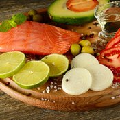 Fresh vegetables and smoked fish on wooden board in rustic kitchen.